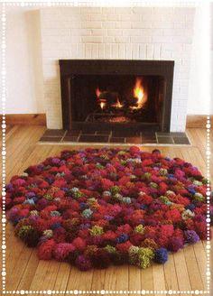 Mãos à obra: faça trocentos pompons de lã, de várias cores...depois, prenda-os numa tela própria para tapeçaria....Um tapete diferente , que você mesmo faz, com alguma dose de paciência.