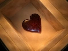 This is a heart in a box. Heart is made only of resin from spruce mixed with red glitter. = )