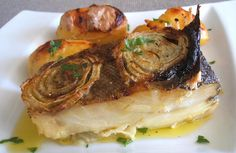 A delicious typical Portuguese recipe of cod in the oven seasoned with salt, pepper, garlics and onion, drizzled with olive oil...