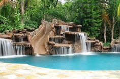 Swimming pool: Waterfall pool slide, It looks natural with the mountains behind it