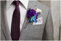 Gorgeous electric blue and purple boutonniere featuring dyed dendrobium orchids, lisianthus and mini calla lily
