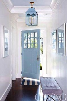 A coastal blue door invites guests into a clean classic foyer.