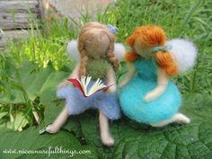 Older needle felt fairy reading a book to the little ginger one. La fatina più grande legge un libro alla piccola fatina coi capelli rossi, feltro ad ago.