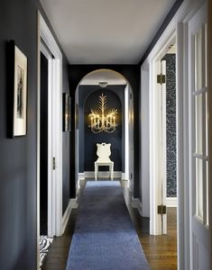Play up the moodiness of an interior hallway by using jet black paint and stark white trim. The dramatic sconce at the end of the hall along with the white chair and white mats on the art all help to light the space.