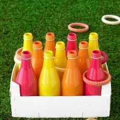 Creating your own ring toss is simple and economical. Here painted bottles are affixed within a citrus crate. Rings can be plates with the centers cut out, embroidery hoops covered in yarn, glow necklaces, rubber bracelets, or many other objects.