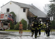 Members of the Freeport Fire Department respond to a house fire down a flooded street in Freeport, New York, on October 29, 2012. (Reuters/Shannon Stapleton)