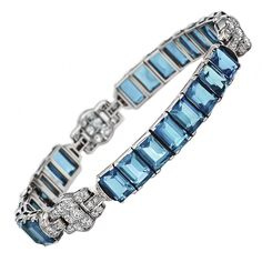 "Dispel the blues with this glorious aquamarine and diamond bracelet. Aquamarines, a ""sea water"" blue stone, was promised by medieval sages to bestow the virtues of insight and foresight to the gem's wearers. A stunning signed bracelet from Oscar Heyman Brothers, circa 1925, showcases 24 aquamarines, 25.00 carats, linked with diamond accents, 1.35 carats, handmade in platinum."