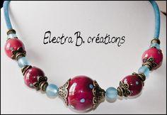 Magnifique collier réalisé avec des perles en polymère aux multiples nuances prune/fuchsia/bordeaux et pois turquoises, finition résine. Elles ont été