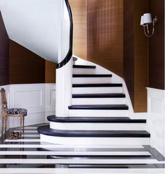 Black and white Italian marble floor, silk wall covering, and black-stained oak stair rail and treads in Day Birger et Mikkelsen's Keld Mikkelsen & Marianne Brandi's Copenhagen home.