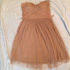 Tan formal strapless dress  This dress is super cute but unfortunately doesn't fit me anymore. This is a great dress that can be dressed up or down just add a few accessories and there you go! feel free to ask any questions and I'm up to take offers also! Size is a small/medium (depending on breast size and hip size) Mystic Dresses Strapless