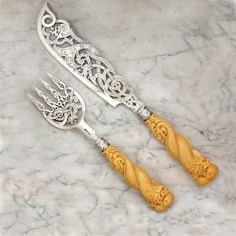 "A Pair of Victorian Antique English Silver Servers London, 1848 by George Adams Length of Fish Slice: 13 7/8"" Length of Serving Fork: 10 1/4"" Each pierced in swirling pattern, engraved with geometric, Japanese style characters, the handle in the form of two intertwined sea serpents rising out of waves."