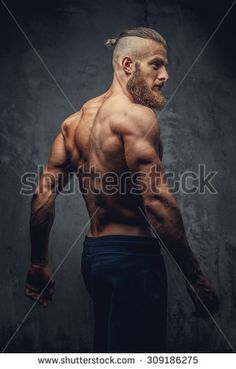 Shirtless muscular man with beard from his back over grey background.