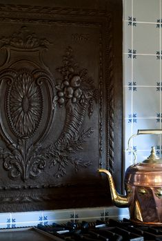 Antique French fireback as backsplash - I could definitely do without that tile, but I love this. Definitely not the tile!