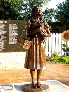 A bronze statue of Dorothy greets visitors at Dorothy's House and the Land of Oz.
