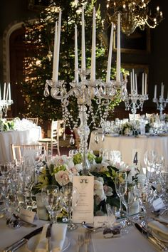 What a difference a centre piece makes to a simple table setting. This is an example of quite an elaborate candleabra - ideal for large, ornate rooms. Note the floral at the base and beads hanging from the candles to bring the piece together, each one set off by the fairy lights in the distance.