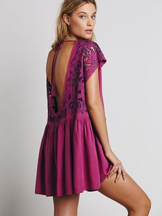 Shapeless mini dress with tonal eyelet embroidery and pleated, ruffled skirt. Deep, scoop back with tassel ties.