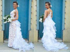 Em tule, o vestido tem fitas mimosa aplicadas formando arabescos. É forrado com tecido nude, realçando ainda mais o artesanato. Nas costas, transparência e profusão de organza, formando uma cauda.