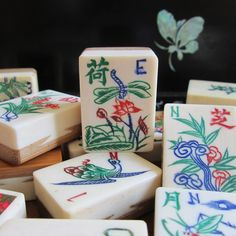 1920s mahjong flower tile, dragonfly motif and other tiles.  Bone and bamboo.  With a black lacquer box in the background.