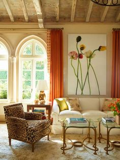 Like certain elements of this room - great architectural detail, pop of color for windows and sofa pillows.  Leopard chair, eye-catching pair of coffee tables.  Swap out artwork and that rug....
