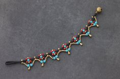 & % HAND WOVEN IN THAILAND This is hand woven bracelet made with dark brown cotton waxed cord weaved together with blue, red seed beads and brass beads. Closure using brass bell & bracelet measures inch long & available in anklet and necklace & Seed Bead Patterns, Beaded Bracelet Patterns, Macrame Bracelets, Ankle Bracelets, Anklet Jewelry, Beaded Anklets, Macrame Jewelry, Bracelet Making, Jewelry Making