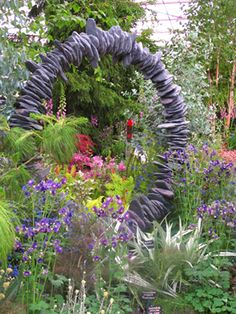 looks likes flat stones with a hole drilled through each one and strung on a round metal hoop. Great gardens have inspiration behind them!