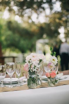 DIY centerpieces with pink, peach, and white flowers.