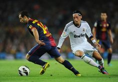 Javier Mascherano (L) of Barcelona shields Mesut Ozil of Real Madrid from the ball during the la Liga match between FC Barcelona and Real Madrid at the Camp Nou stadium on October 2012 in Barcelona, Spain. Barcelona Vs Real Madrid, Fc Barcelona, Sports Highlights, Camp Nou, Fifa World Cup, October 7, Soccer, Game, Watch