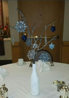 Winter wonderland centerpieces with recycled wine bottles and branches. Really cost efficient!