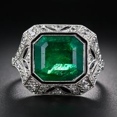 This dramatically beautiful Art Deco-Style ring, hand crafted in platinum and diamonds with black onyx and enamel accents, is designed around a deep green, but admittedly average quality (mostly opaque), emerald cut emerald measuring 3.20 carats. The verdant gemstone is dressed up on all four sides in full Art Deco splendor in an artfully sculpted geometric mounting adorned with decorative open work details, small sparkling old mine-cut diamonds and navette shape black onyx calibre