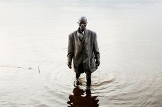 Un pêcheur habillé pour la messe dominicale marche dans la rivière Oubangui, tôt le matin