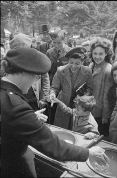 War Fair: Holidays at Home at a fete in Russell Square, London, 1943. A young boy, helped by his mother, enjoys a game of magnetic fishing at a stall run by a member of the Red Cross at the Russell Square fete. Civilians and a member of the Royal Air Force look on. #wartime #WW2 #history