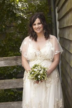 plus size bride wearing a romantic lace wedding dress by Claire Pettibone. I love the sheer flutter sleeves.