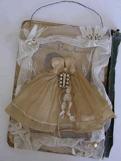 I can't believe how cute this is...altered doll dress on a vintage book cover