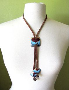 Copper enamel and suede bolero-style necklace is from the late 60s or early 70s. Very cool Hippie Chic piece of vintage jewelry. The slide measures 1.5 square and the end pieces measure 1. They are strung on a 1/4 wide piece of leather. The sueded side is showing, the leather finish on the other side has an area that is cracked. If you prefer the leather look, you can wear that side out. It would be easy enough to hide the cracked part behind the slide piece. Thanks for looking! vinta...