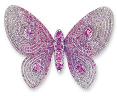 AN UNUSUAL PINK SAPPHIRE AND DIAMOND BROOCH, BY WALLACE CHAN – Photo c/o Christie's DESIGNED AS A BUTTERFLY, THE BODY SET WITH A ROW OF PEAR AND RECTANGULAR-SHAPED PINK SAPPHIRES, WITHIN A BRILLIANT-CUT DIAMOND SCALLOPED BORDER, ACCENTED BY REVERSE-SET BRILLIANT-CUT DIAMOND PRONGS, JOINED TO THE FLEXIBLE WINGS, EACH SET AT THE CENTRE WITH A RECTANGULAR-SHAPED PINK SAPPHIRE, WITHIN AN OPENWORK CIRCULAR-CUT GRADIENT PINK SAPPHIRE CONCENTRIC SURROUND, MOUNTED IN TITANIUM AND 18K WHITE GOLD ~