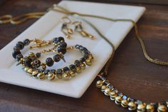 ExVoto Jewelry. Created in the USA from vintage elements.  Tiny Indian bells, glazed glass beads, inlaid bone beads and brass charms.