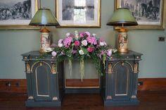 Long and low arrangement on a beautiful antique dresser.
