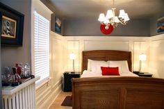 I love the wainscoting in this room and the contrast with the darker wall although I wouldn't paint mine dark gray. I don't think the style of the bed fits very well with the color scheme, but if the wall color had been warmer it would have been fine.