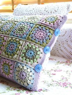Granny Square Pillow Top and Re-cycled Sweater Piece For The Back. Embellished with buttons on the sides.  (not a pattern, but the designer gives an explanation of her work on Ravelry)