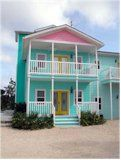 soft teal beach house on sand. Cute pink & yellow accent