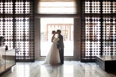 bride and groom kiss in lobby of mid-century modern hotel @myweddingdotcom
