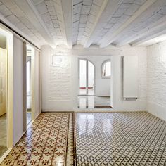 Polished mosaic floors reveal the original room layout of this renovated apartment in Barcelona by local studio Vora Arquitectura