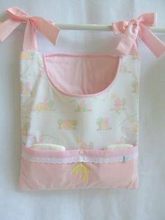 1 porta fralda. <br>Feito em tecido de algodão com manta acrílica e bordado a máquina. <br>Com alças para amarrar no berço ou colocar no varão, facilitando a troca de fraldas do bebê. <br> <br>O produto é feito sob encomenda. Consulte antes. <br>Medidas: <br>34 cm x 39 cm sem contar com as alças.