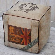 POSTAL STAMP SQUARE OTTOMAN  Looking for a way to introduce Cool Britannia to your interior design? Look no further than our Postal Stamp Square Ottoman. Vintage prints of stamps are balanced with the neutral recycled army tent canvas and leather piping.