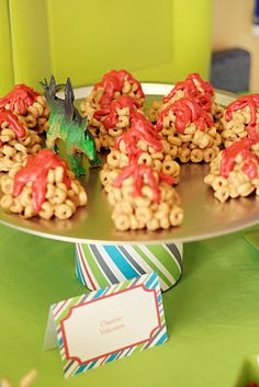 """These Cheerio Snacks and right away were the """"volcanos"""". After letting them cool, topped them off with red wiltons melting candy, heated it per the bag instructions, added it to a ziploc baggie, snipped the tip off, and squeezed on took to make the lava.  Recipe found here - http://kathiecooks.blogspot.ca/2010/01/cheerio-treats.html"""