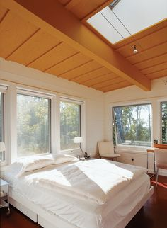 In a vacation cabin on Madeline Island, a few miles off the coast of Wisconsin, skylights and huge windows flood the master bedroom—and every room in the house—with sunlight. Architecture by David Salmela. Bed by Techline; lighting by Tech Lighting. Photo by Chad Holder