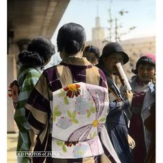 This photo, taken in Tokyo in May 1934, shows two girls wearing a kimono, and two more girls wearing western style clothes, one of them a middy suit and a hat. The girl with her back towards the photographer is wearing an obi (the beautifully decorated sash used to tie the kimono) which must have been quite modern at the time.