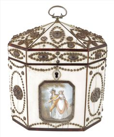 A George III ivory and cut steel octagonal tea caddy, with tortoiseshell edging, the front with a painted plaque depicting a lady and man wearing a plumed hat, loop handle to both lids, 5in (12.6cm) high, 4¼in (10.8cm) wide, 3in (7.6cm) deep.