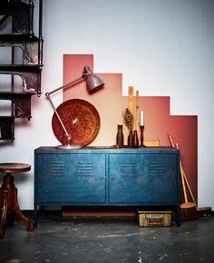 Un mobile di metallo da poco rinnovato davanti a una parete dipinta con un motivo geometrico - IKEA
