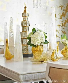 A vignette of crystal obelisks and golden glass vases creates an opulent scene in this dining room - Traditional Home® / Photo: Emily Followill / Designer: Melanie Turner